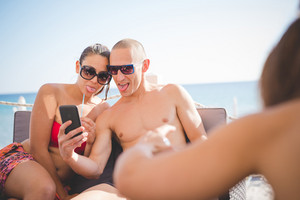 group of young multiethnic friends women and men at the beach  in summertime using smartphone taking selfie while having an aperitif - happy hour, relax concept