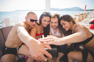 group of young multiethnic friends women and men at the beach  in summertime using smartphone taking selfie while having an aperitif - social network, technology concept