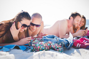 group of young multiethnic friends women and men at the beach in summertime using; smartphone