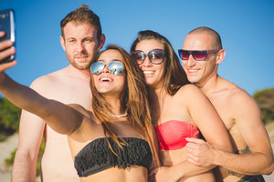 group of young multiethnic friends women and men at the beach in summertime using smartphone