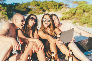 group of young multiethnic friends women and men at the beach in summertime using tablet taking selfie doing grimace - technology, vanity, social network concept