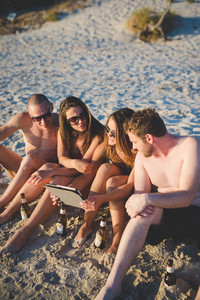 group of young multiethnic friends women and men at the beach in summertime using tablet
