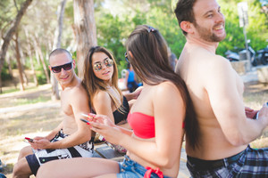 group of young multiethnic friends women and men at the beach in summertime using technological devices smartphone and tablet - social network, technology, relax concept