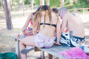 group of young multiethnic friends women and men at the beach in summertime using technological devices smartphone and tablet