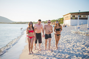 group of young multiethnic friends women and men at the beach in summertime waliking on the foreshore smiling from front with beers in their hands - team, friendship, tourism concept
