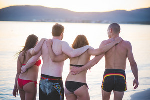 group of young multiethnic friends women and men at the beach in summertime walking hugging on the foreshore from back - team, friendship, tourism concept