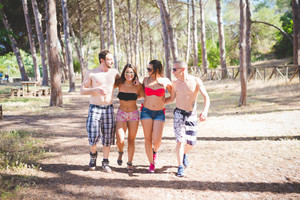 group of young multiethnic friends women and men at the beach in summertime walking hugging