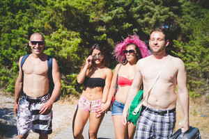 group of young multiethnic friends women and men at the beach in summertime walking in swimsuit through the beach in swimsuit