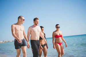 group of young multiethnic friends women and men at the beach in summertime walking through the foreshore