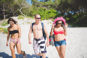 group of young multiethnic friends women and men at the beach in summertime walking