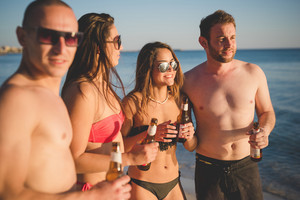group of young multiethnic friends women and men at the beach in swimsuit drinking some beers while watching sunset on the foreshore - friendship, carefreeness, relaxing concept