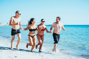Group of young multiethnic friends women and men running on the seashore hand in hand, having fun, laughing- friendship, summertime, happiness concept