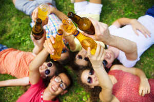 Group of young people having fun in park, lying on the grass with drinks