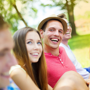 Group of young people having fun in park, sitting on the grass