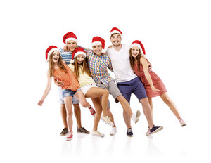 Group of young people in santa hats having fun, isolated on white background