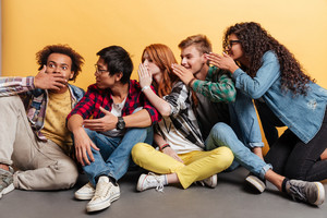 Group of young people surprising and telling secrets to each other over yellow background
