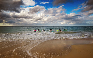 Group of young surfers on the beach with blue sky and white cloud summer morning offer shade to picnickers in this iconic coastal city in south Western Australia.