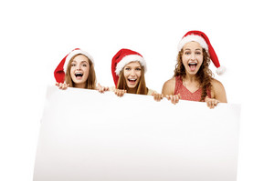 Group of young women in santa hats holding copy space, isolated on white background