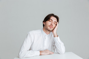 Hadsome young man in white shirt sleeping while sittng at the desk isolated on the gray background