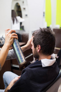 Hair styling by a professional barber. Unrecognizable professional hairdresser making new haircut to her handsome client. Man at barbershop.