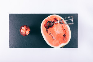Half a ripe watermelon, slices in a glass and an ice cream spoon on a white table top view