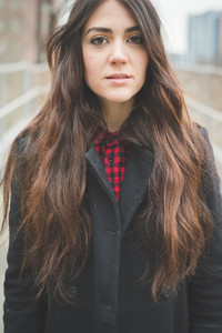 Half lenght of a young beautiful brunette long hair pensive woman living the city in winter outdoor - concept of humans emotions -  dressed with black coat and checked red shirt