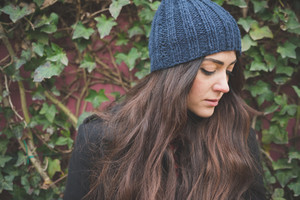 Half lenght of a young beautiful brunette long hair pensive woman posing in the city in winter outdoor looking downward - concept of humans emotions