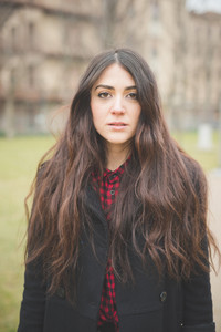 Half lenght of a young beautiful brunette  long hair pensive woman posing the city in winter outdoor - concept of humans emotions