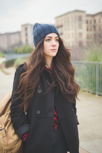 Half lenght of a young beautiful brunette long hair pensive woman walking in the city in winter outdoor - concept of humans emotions