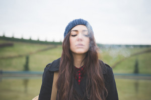 Half lenght of a young beautiful brunette woman long hair pensive and melancholic smoking cigarette looking downward - concept of human emotions