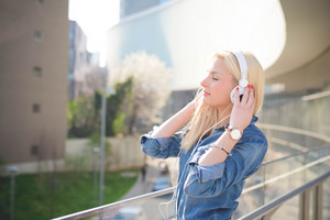 Half lenght of a young beautiful caucasian blonde girl listening to music in the city with headphones leaning on a windowsill with eyes closed- relax, youth, emancipation concept