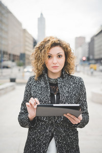 Half lenght of a young beautiful caucasian contemporary businesswoman walking through the streets of the city using a tablet looking camera - technology, network, business, finance concepts