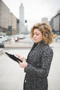 Half lenght of a young beautiful caucasian contemporary businesswoman walking through the streets of the city using a tablet looking the screen - technology, network, business, finance concepts