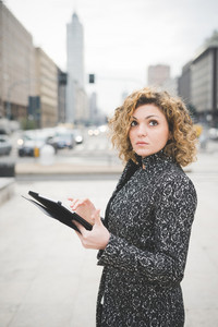 Half lenght of a young beautiful caucasian contemporary businesswoman walking through the streets of the city using a tablet overlooking- technology, network, business, finance concepts