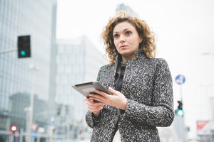 Half lenght of a young beautiful caucasian contemporary businesswoman walking through the streets of the city using a tablet overlooking - technology, network, business, finance concepts