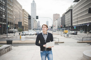 Half lenght of a young handsome caucasian contemporary businessman standing on the street using a notebook overlooking - technology, network, business, finance concepts