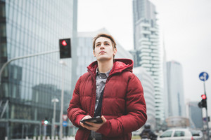 Half lenght of a young handsome caucasian contemporary businessman walking through the city using a tablet overlooking - technology, network, business, finance concepts