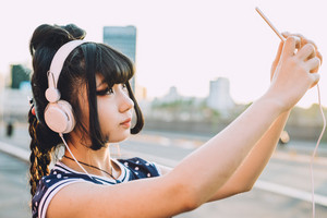 Half lenght of young beautiful asian millennial woman nonconformist outdoor in city back light listening music with headphones and taking selfie with smart phone hand hold - technology, music, social network concept