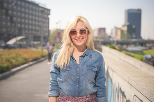 Half length of a young beautiful blonde caucasian girl posing outdoor in the city wearing a jeans shirt and a floral skirt looking in camera smiling - youth, carefreeness, freshness concept