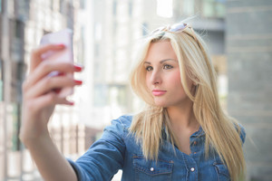 Half length of a young beautiful blonde caucasian girl using a smart phone taking a selfie - communication, technology, social network concept