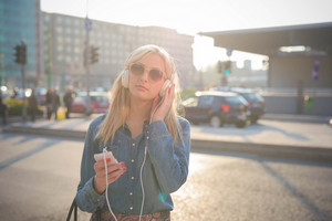 Half length of a young beautiful caucasian blonde girl listening to music in the city with headphones looking in camera,- relax, youth, emancipation concept