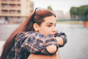 Half length of a young beautiful reddish brown hair caucasian girl leaning against a windowsill overlooking - pensive, youth, freshness concept - dressed with checked shirt