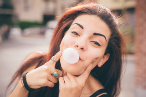 Half length of a young beautiful reddish brown hair caucasian girl posing in the street playing with bubblegum looking camera- childhood, freshness, carefreeness concept - dressed with black shirt