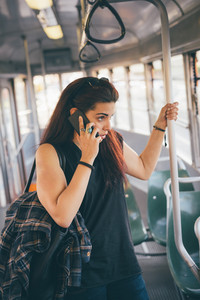 Half length of a young beautiful reddish brown hair caucasian woman talking smartphone on a tram - technology, social network, communication concept - overlooking