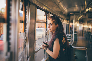 Half length of a young beautiful reddish brown hair caucasian woman using a smartphone on a tram - technology, social network, communication concept - overlooking