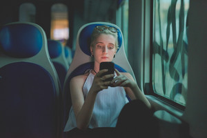 half length of a young handsome caucasian blonde italian designer sitting in a train, holding a smartphone, looking down the screen, smiling - technology, social network, communication concept