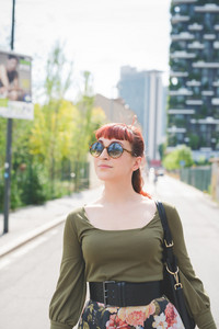 Half length of a young handsome caucasian redhead woman posing in the city, overlooking right, smiling - pin up, carefreeness concept - wearing green shirt, floral skirt, bag and sunglasses