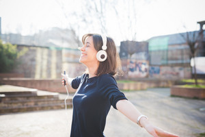 Half length of a young pretty brown hair caucasian girl listening music with headphones, holding a smartphone in her hand, overlooking right, dancing and smiling - music, relaxing, happiness concept