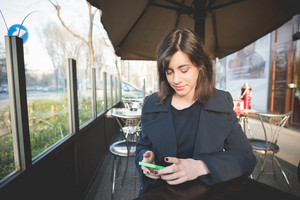 half length of a young pretty woman sitting at the bar using smartphone, looking downward and tapping the screen - technology, social network, communication concept