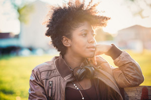 Half length of beautiful black curly hair african woman listening music with headphones in city back light - music, technology, serenity concept